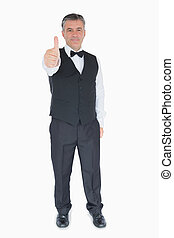 Smiling man in suit showing thumbs up