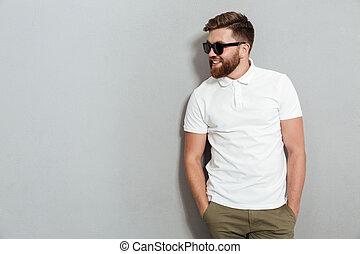 Smiling man in sunglasses posing in studio