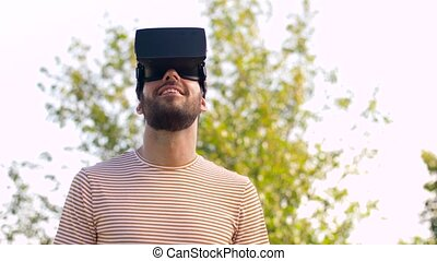 smiling man in virtual reality headset outdoors -...