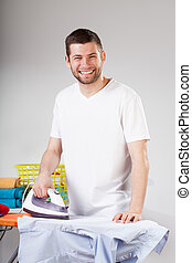 Smiling man ironing