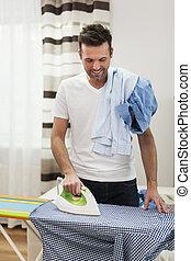 Smiling man ironing his shirts