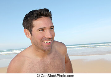 Smiling man jogging on a sandy beach