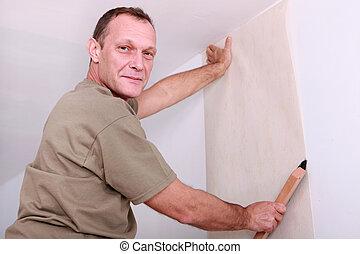 Smiling man laying wallpaper