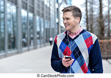 Smiling man listens music in a street