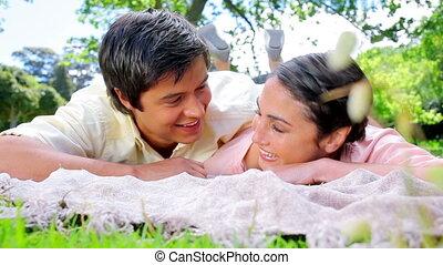 Smiling man looking at his girlfriend napping