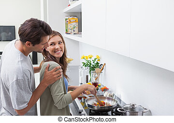 Smiling man looking at his wife who is cooking vegetables