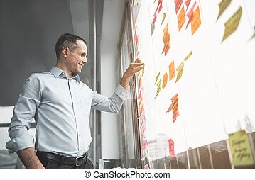 Smiling man looking at sticky notes