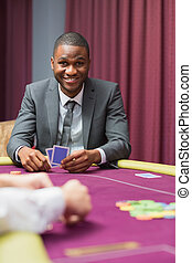 Smiling man looking up from poker