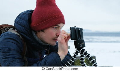Smiling man looks at the phone on a tripod and touches the screen in winter, 4K.