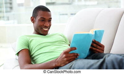 Smiling man lying on couch reading