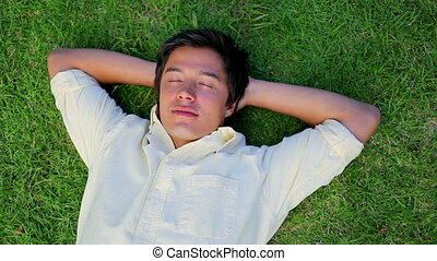 Smiling man lying on the grass