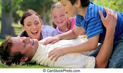 Smiling man lying on the grass with his family in the ...
