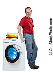 smiling man near the washing machine and a stack of bright linen, isolated on white background