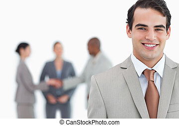 Smiling man of business with trading partners behind him