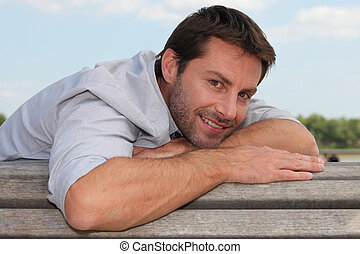 smiling man on a bench