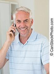 Smiling man on a phone call looking at camera