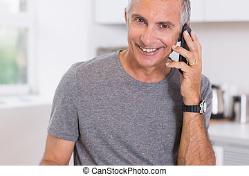 Smiling man on the phone in the kitchen