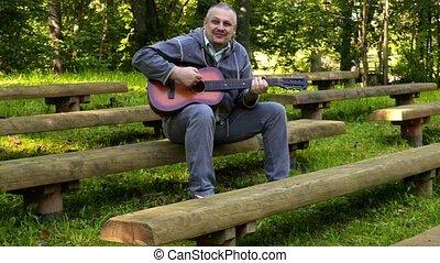 Smiling man playing guitar in park