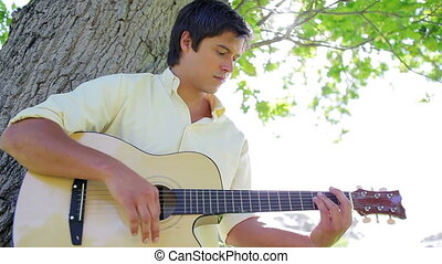 Smiling man playing music with his acoustic guitar