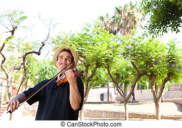 Smiling man playing violin outside