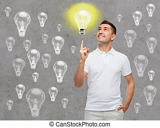 smiling man pointing finger up to lighting bulb - happiness,...