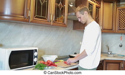 Smiling man preparing salad in the kitchen. man preparing...