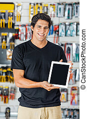 Smiling Man Presenting Digital Tablet In Hardware Store