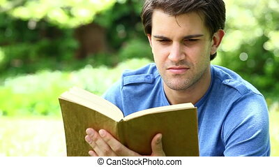 Smiling man reading a fascinating book