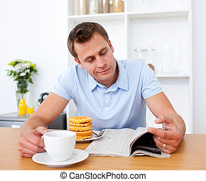 Smiling man reading a newspaper while having breakfast