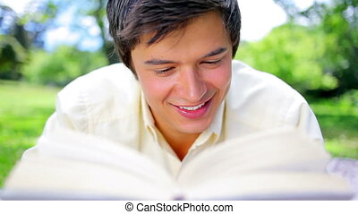 Smiling man reading an interesting novel in a parkland