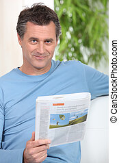 Smiling man reading newspaper on a couch