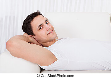 Smiling Man Relaxing On Sofa At Home