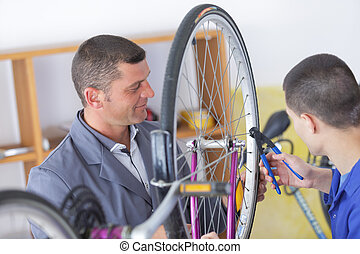 smiling man seller in uniform talking to apprentice