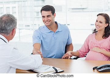 Smiling man shaking hands with his doctor while holding his expecting wifes hand in bright surgery