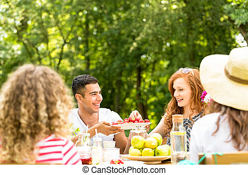 Smiling man sharing strawberries with a beautiful girl while having lunch in the garden