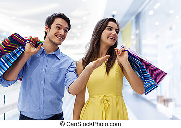 Smiling man showing something woman in the shopping mall