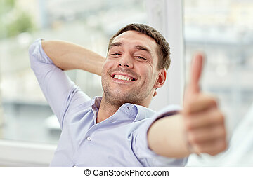smiling man showing thumbs up at home or office