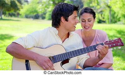 Smiling man singing while playing the guitar