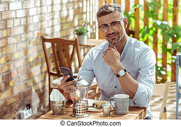 Smiling man sitting at the cafe table and drinking tea.