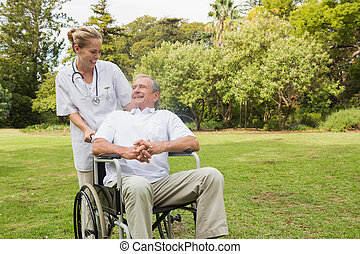 Smiling man sitting in a wheelchair talking with his nurse pushing him at the park