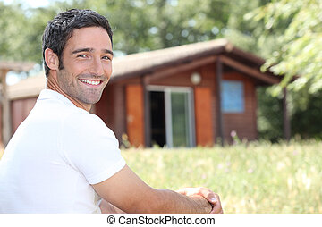 Smiling man sitting in front of a cabin