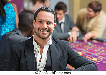 Smiling man sitting leaning on roulette table