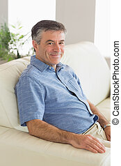 Smiling man sitting on a sofa