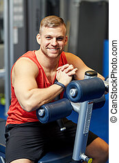 smiling man sitting on exercise bench in gym
