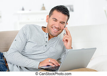 smiling man sitting on sofa with laptop and phone