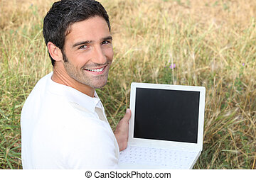 Smiling man sitting on the grass with a laptop computer