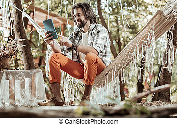 Smiling man sitting with tablet in a hammock