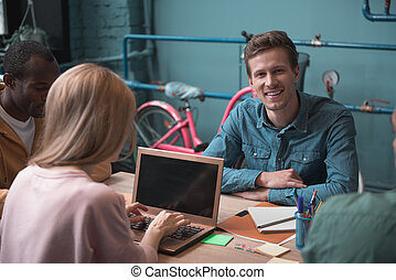 Smiling man situating near colleagues at desk