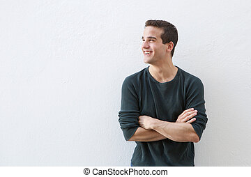Smiling man standing against white background with arms crossed