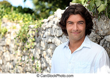 Smiling man standing in front of a stone wall